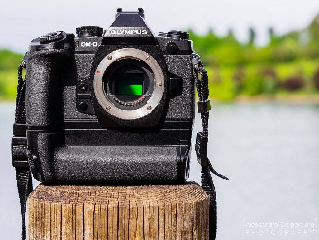 Olympus OM-D E-M1 mirrorless camera near a lake. Tropicalized and dust resistant. 5-axis image stabilization, electronic viewfinder.
