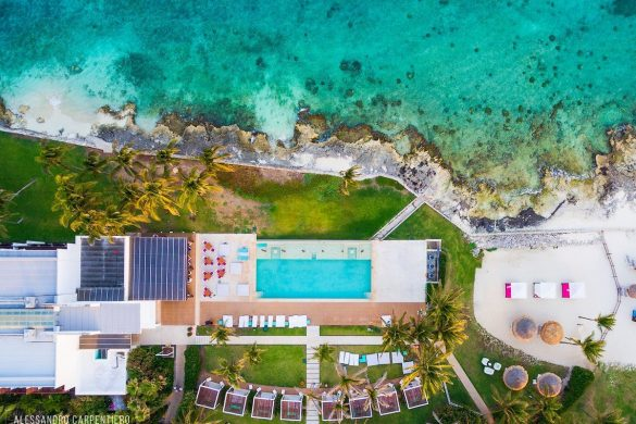 drone shot of a swimming pool and the ocean